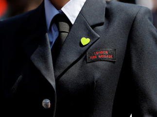 A member of the London Ambulance Service wears a green 'Grenfell' heart badge at a dedication service for the St Clement Garden of Peace and Healing remembering those affected by the Grenfell Tower fire at St Clement's Church in west London