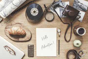 Stylish composition of flat lay on wooden desk with laptop, map,  cup of coffee, phone, croissant  notebook, camera and office accessories. Creative desk of photographer. Blank paper for inscription.