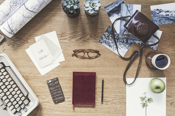 Modern composition of flat lay on wooden desk with typewiter, photos, notebook, retro camera , map and office accessories. Creative desk of traveler and adventure man.
