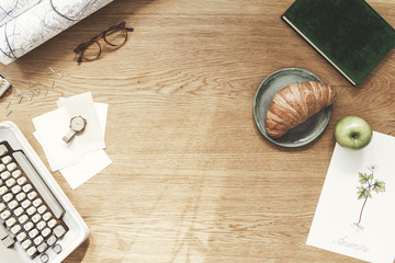 Stylish composition of flat lay on wooden desk with croissant, map, floral poster, notebook and office accessories. Creative desk of traveler, poet, writer with copy space.