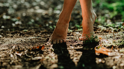 Young girl walking barefoot in the secret botanic garden. Close up image of female bare feet touching soil and green grass in the forest.