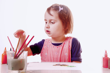 Little cute child girl holding a paint brush and painting on a white wall background (Creativity, education, child development in art, happy childhood, abilities concept)