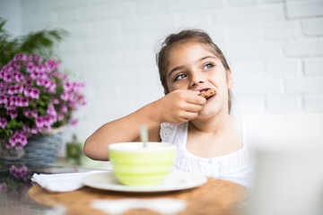 Crop view of little cute girl eating tasty cookie with chocolate at table at blurred background with flowers
