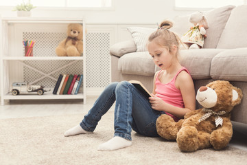 Lttle girl and her teddy bear reading book