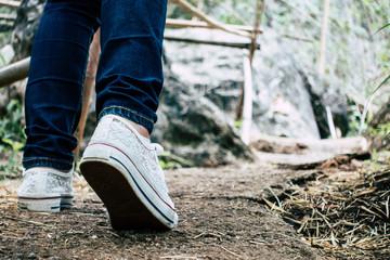 woman's feet walking in nature trail