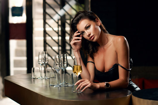 Elegant young woman sitting in bar and having good time alone. Pretty brunette girl in black leather dress. Lady drinking glass of wine.