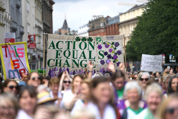 Women wear the suffragette colours of green, white and violet - standing for Give Women Votes - as they march in the 'Processions' women's march in Belfast