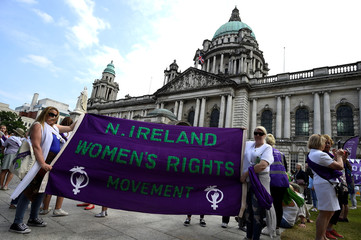 Women hold a banner decorated with the suffragette colours of green, white and violet - standing for Give Women Votes - as she marches in the 'Processions' women's march in Belfast