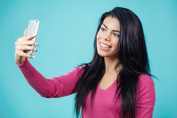 close up portrait of attractive smiling woman with black hair using her smartphone for selfie to photograph her hairstyle