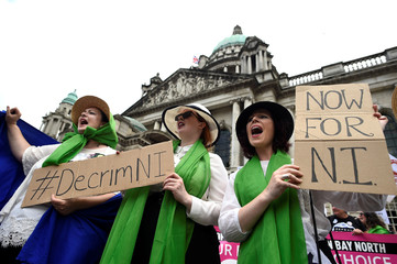 Women hold banners and wear clothes in the suffragette colours of green, white and violet - standing for Give Women Votes - as they march in the 'Processions' women's march in Belfast