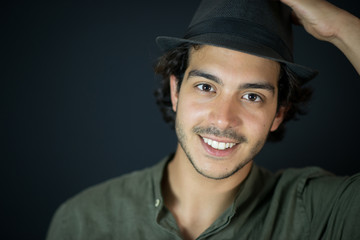 A nice young man, 20Y, is posing in studio with a hat. Black background.