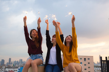 Asian group of friends lighting sparklers and enjoying freedom at sunset,asian woman holding sparklers happily on rooftop