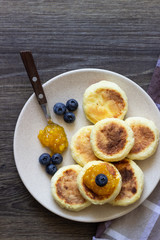 Cottage cheese pancakes (syrniki) with sour cream, orange jam and fresh blueberries on a plate. Breakfast or lunch concept.