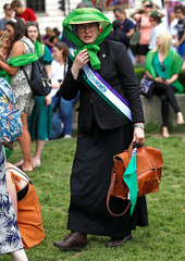 A woman wears the suffragette colours of green, white and violet - standing for Give Women Votes - in the 'Processions' women's march in Westminster, London
