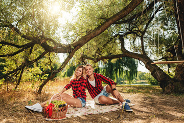 Young couple on a picnic in a park near a tree with wine and fruit