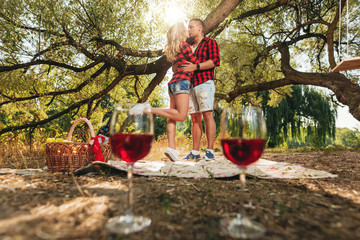 Young man and woman on a picnic. In the foreground glasses with wine, in the center of the frame a couple in love
