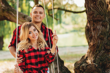 Amorous couple on romantic date on swings outdoor