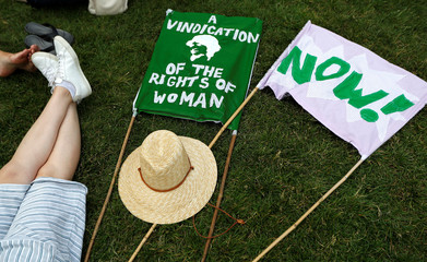 Banners in the suffragette colours of green, white and violet - standing for Give Women Votes - lie on the grass next to the statue of Millicent Fawcett during the 'Processions' women's march in Westminster, London