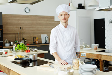 Young chef in uniform standing by his workplace while cooking something on electric stove