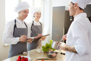 Happy young man and woman in chef uniform making notes while listening to their master in the kitchen