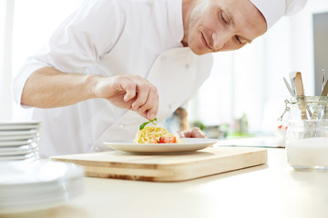 Chef putting basil leaf on top of pasta pile before serving it to client