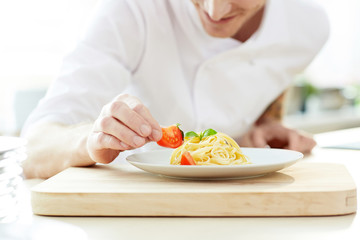 Young chef decorating pasta with fresh tomato pieces before serving