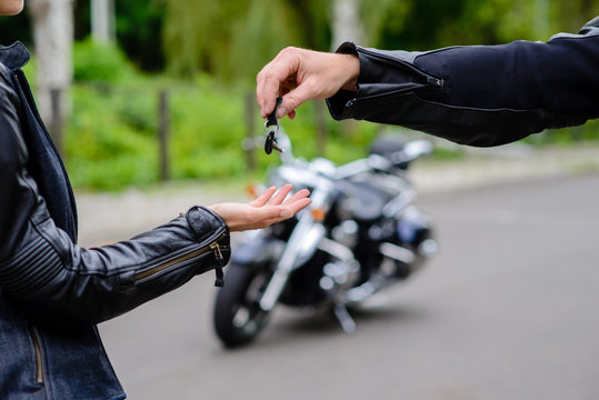 Hands give the keys to the motorbike. The concept of selling and renting motorcycles.