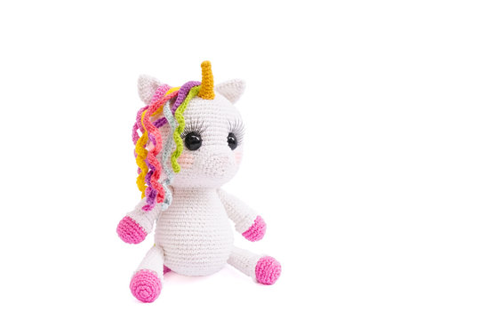 Unicorn plush doll isolated on white background. A crochet doll of a white unicorn. Amigurumi of cute animal.