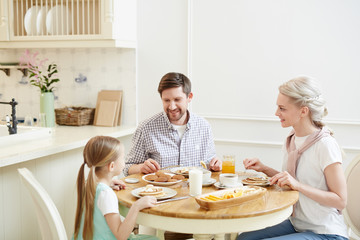 Young parents and little daughter sitting by served table, eating breakfast and talking