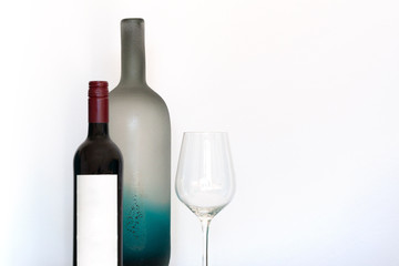 Wine bottle with empty label, wineglass and decorative frosted glass bottle on white background with copy space