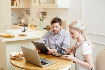 Young husband with document and wife with calculator counting family budget in the kitchen in front of laptop