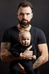 Handsome tattooed beared man in black t-shirt, looking at camera with serious face, holding cute little baby on black background
