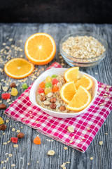 Homemade oatmeal porridge with orange, candied fruit and hazelnut on grey wooden background. Healthy breakfast.