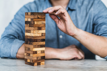 hand pull important color block from balance wooden stack business organize  strategy and risk management control concept