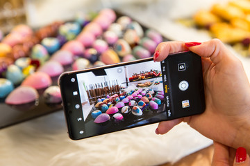 Food blogging concept. Hand with smartphone photographing a colorful cakes