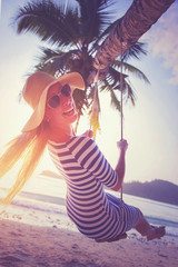 Young woman swinging on the beach and smiling into camera at sunset. Vacation concept. Retro styled colors.