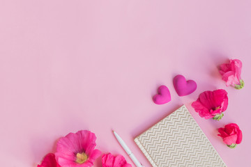 Flat lay desk with pink flowers and notebook