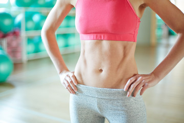 Midsection of young slim sporty woman in activewear in akimbo pose