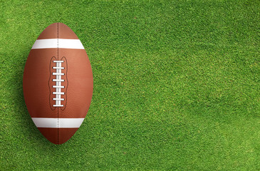 American football ball on grass field background. Football ball 3D illustration.