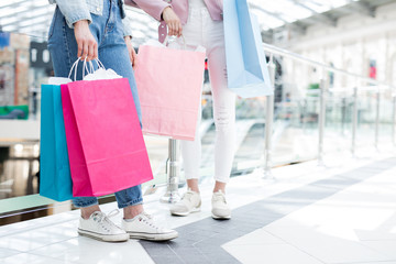 Close-up of unrecognizable hipster girls in sneakers and jeans holding bright shopping bags from concept stores while walking over mall