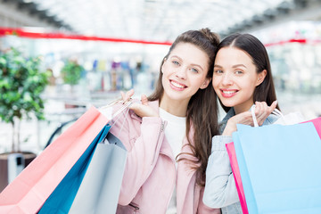 Cheerful excited beautiful female friends holding heap of shopping bags and looking at camera while enjoying shopping in mall