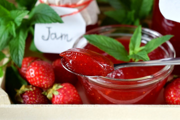 Strawberry jam in glass jars surrounded by the berries and mint in a wooden box