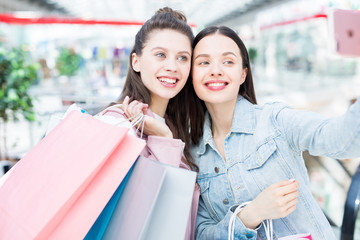 Smiling attractive young women in casual clothing photographing together while having fun in shopping mall and buying clothes