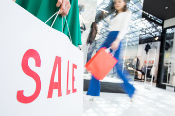 Focus on sale inscription written on shopping bag, blurred motion of stylish girl walking in mall
