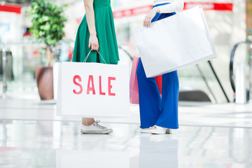 Unrecognizable girls in stylish clothes holding big shopping bag while buying clothes on seasonal sale in mall