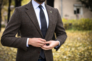 Man in custom tailored suit posing outdoors in autumn and buttoning his coat