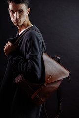 Young confident prosperious businessman dressed in trendy top coat wearing a brown leather bag. Man Clothing and Accessories and Fashion concept.