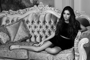Young beautiful tanned woman with long wavy hair in luxurious black evening dress sitting at bed in luxury interior
