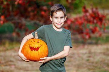 smiling child and carved scary face on a pumpkin. portrait of a boy with a Halloween pumpkin in his hands. Blurred background. copy space for your text