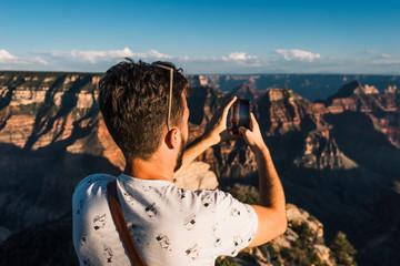 man take photo of Grand Canyon with blue sky in Arizona, USA.